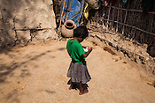 4 year old Radha stands with a bowl of food in the courtyard of her house in Saptari, Nepal. <br /> Asha Devi got married when she was 14. She got pregnant after 6 months of her marriage. Her first child survived for 6 days, she woke up next to a dead baby. She was pregnant two months later. Asha Devi's 2nd daughter survived for 9 months and later died due to prolonged fever. 3 months after her daughter died, Asha was pregnant again and within w months, she had spontaneous abortion. She was pregnant with Radha Kumari mandal who was acutely malnourished. Radha was admitted when she was 36 months old on October, 20th 2013. MUAC - 110 mm, Weight - 7 kg, Height - 75 cm. Radha was discharged on Dec 6, 2013 - her MUAC at the time of discharge was 128mm, Weight 8.8kg and height- 75.5 cm. She consumed 100 sachets of RUTF and gained 5gm/day while on the programme. <br /> Rukmini, her second daughter was born a year after Radha was born. Rukmini was severely malnourished too. She was admitted on Feb 16th, 2014. Her MUAC was 119mm, weight - 11 kg, and height - 96 cm. Her third daughter Sharda is severely malnourished. Sharda is under RUTF.  <br /> Asha Devi is pregnant for the 7th time and is 6 months pregnant.
