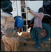 Sahara desert, Libya-Chad, November/December 2004..Every week, a convoy of 40 privately owned Libyan trucks loaded by the WFP with about 1000 metric tons of western food aid cross 2500 km of deep desert across Libya and Chad to reach more than 200 000 refugees from Darfur in camps near the Sudanese border. A transmission belt pulley has broken, causing a truck to seriously overheat, the mechanic will 'make' a replacement and fix the problem...