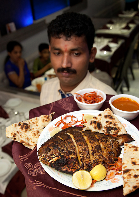 MUMBAI, INDIA - SEPTEMBER 27, 2010: The famous pomfret pepper tandoori with onion salad, naan, chutney and 'sauce' at  Mahesh Lunch Home in the Mumbai suburb of Fort. The Taj Mahal Palace and Tower Hotel in Mumbai has re-opened after the terror attacks of 2008 destroyed much of the heritage wing. The wing has been renovated and the hotel is once again the shining jewel of Mumbai. pic Graham Crouch