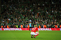 Jonathan Williams of Wales sits on the ground dejected while Ireland players celebrate their win in the background during the FIFA World Cup Qualifier Group D match between Wales and Republic of Ireland at The Cardiff City Stadium, Wales, UK. Monday 09 October 2017
