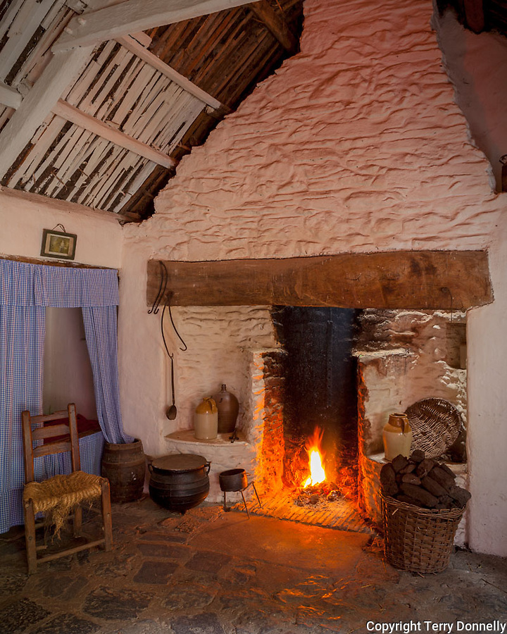 County Clare, Ireland<br /> Hearth with peat fire in a restored stone cottage, Bunratty Folk Park