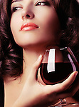 Portrait of a beautiful young woman holding a glass of red wine in her hand Image © MaximImages, License at https://www.maximimages.com