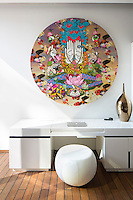 A circular Thai-inspired artwork hangs on the wall of the bedroom suite above a contemporary desk in the Villa Bianca at Iniala