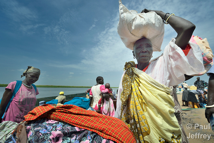Displaced women disembark from a boat that has brought them back home to Bor, a city in South Sudan's Jonglei State that has been the scene of fierce fighting in recent months between the country's military and anti-government rebels. After fighting broke out in mid December 2013, control of the town changed hands four times in a few weeks. ACT Alliance members were among the first humanitarian agencies to enter the city in January 2014, and are providing services to thousands of people who are cautiously returning home to the troubled city. These women have crossed the While Nile River from Awerial, where they took refuge.