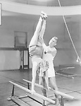 Coach helping woman on parallel bars
