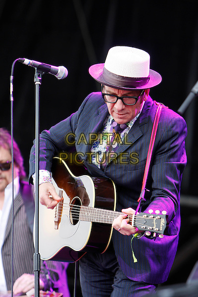 ELVIS COSTELLO.Performing live at Hard Rock Calling, Hyde Park, London, England..June 27th, 2010.half length stage concert live gig performance music black jacket guitar white hat glasses polka dot tie .CAP/MAR.© Martin Harris/Capital Pictures.