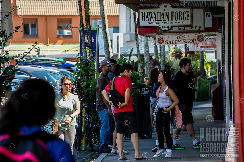 Visitors and residents shop and converse along the waterfront by Kamehameha Avenue in downtown Hilo, Big Island of Hawai'i.