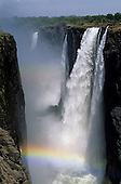 Victoria Falls, Zambia and Zimbabwe border. The waterfall in the gorge with a rainbow from the mist.