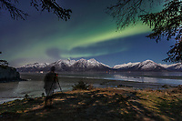 winter landscape shows photographer taking photos of Northern Lights (Aurora Borealis) in sky above moonlight on the Chugach Mountains that jut above Indian area and Turnagain Arm taken from Hope   Seward Highway January 2014