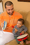 Young father and 16 month old toddler son playing with musical instruments baby hitting tambourine like a drum