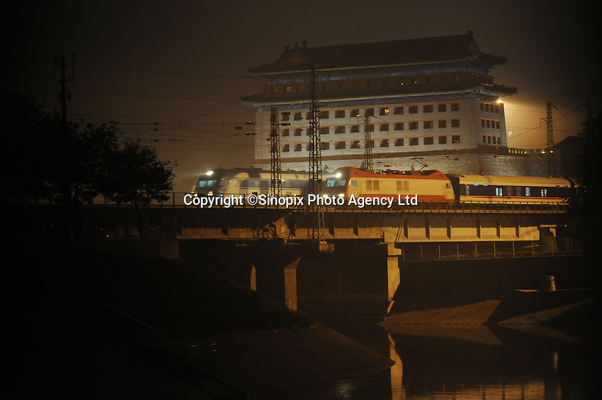 At night, trains pass by the city of Beijing...., the building behind is the ancient Tower of Beijing City Wall which located south of Jianguomen, southeast of Beijing railway station, Beijing, China..30 Aug 2010