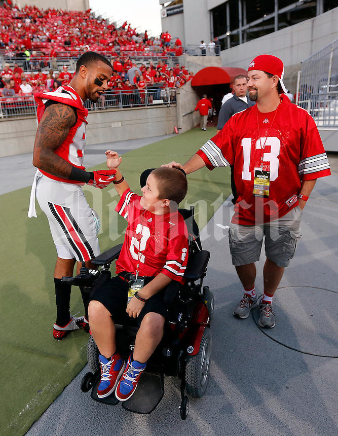 Ohio State Buckeyes wide receiver Chris Fields (80) greets fan Jacob Jarvis, 13, and his step-dad Chad Studebaker of Delaware prior to the game between Ohio State and Wisconsin at Ohio Stadium on Saturday, September 28, 2013. (Columbus Dispatch photo by Jonathan Quilter)
