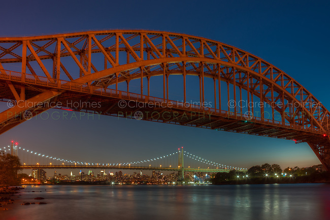 The Hell Gate and Triborough (Robert F. Kennedy) Bridges span the Hell Gate tidal strait in the East River from Randall's/Wards Island to the borough of Queens in New York City, as the last hint of the setting sun fades into the western sky during evening twilight.  The skyline of Manhattan can be seen in the background.