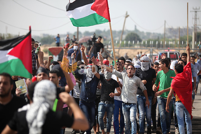 Palestinian protesters shot slogans during clashes with Israeli security forces next to the border fence with Israel, at the Erez crossing in the northern Gaza strip, on October 13, 2015. A wave of stabbings that hit Israel, Jerusalem and the West Bank this month along with violent protests in annexed east Jerusalem and the occupied West Bank, has led to warnings that a full-scale Palestinian uprising, or third intifada, could erupt. The unrest has also spread to the Gaza Strip, with clashes along the border in recent days leaving nine Palestinians dead from Israeli fire. Photo by Ashraf Amra