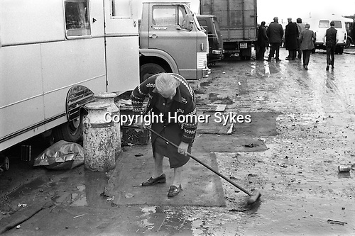 Appleby in Westmorland Horse Fair Cumbria.  Older woman trying to keep her caravan clean atfer heavy rain fall. 1981.