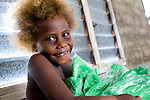 A young child grins over his family's new mosquito nets, provided by the Solomon Islands Red Cross to help prevent malaria.<br /> <br /> With little access to clinics or hospitals, preventative measures such as these are critical for saving the lives of children and their families.