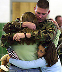 Kourtney McPhail, 9, of Palm Coast, clings to her mom, Izzy, and her dad, Staff Sgt. Philip McPhail, as they share a farewell hug, Saturday, Dec. 13, 2003, at the Florida National Guard Armory in St. Augustine.  Sgt. McPhail, and his wife, Izzy, also a Seargent with the Florida National Guard, are no strangers to saying goodbye to each other.  Izzy just returned from a deployment to Guantanomo Bay Cuba and now Philip will be heading to Iraq.(Brian Myrick)