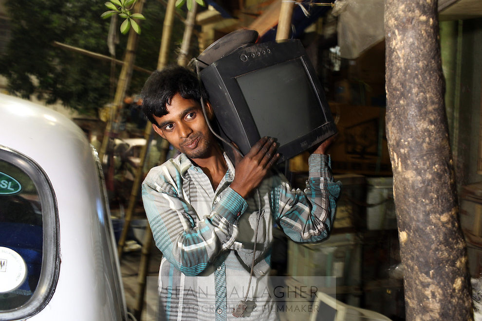 A worker at the Chandni Chowk secondhand electronics market carries a computer monitor, which will later be broken down and recycled. Kolkata, India. November, 2013