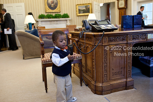 Corbin Fleming, brother of 2011 March of Dimes National Ambassador Lauren Fleming, plays with the President's telephone during his family's visit to the Oval Office, February 7, 2012. .Mandatory Credit: Pete Souza - White House via CNP