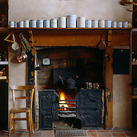 A row of antique storage jars in descending size sits on the rustic mantelpiece above the original kitchen range