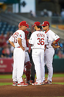 Springfield Cardinals pitching coach Jason Simontacchi (46) talks with pitcher Arturo Reyes (36) as catcher Alberto Rosario (hidden) and Aledmys Diaz look on during a game against the Frisco RoughRiders  on June 3, 2015 at Hammons Field in Springfield, Missouri.  Springfield defeated Frisco 7-2.  (Mike Janes/Four Seam Images)