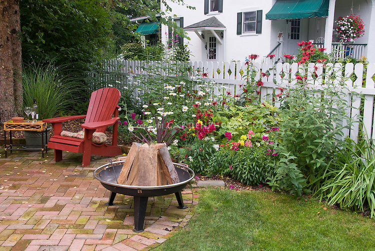 Cooking Fire in Backyard with brick patio, Adirondack chair, plants and flowers, house, fence