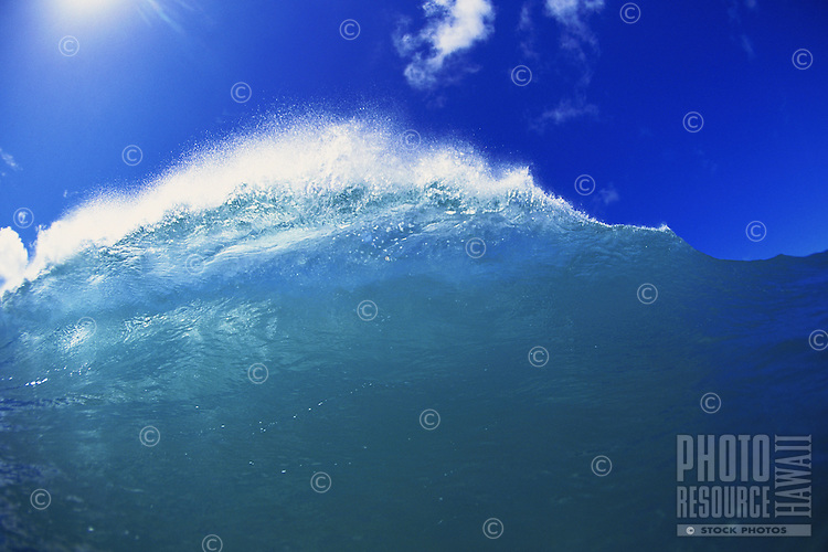 Backlit wave cresting over shallow reef with blue skies in background.