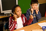 Education elementary Grade 3 science classroom male and female students sitting  side by side using tuning forks horizontal