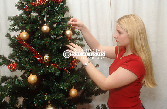 Teenage girl decorating Christmas tree with tinsel and baubles,