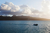 FRENCH POLYNESIA, Vahine Island. View of a boat and Tahaa Island in the background at dusk.