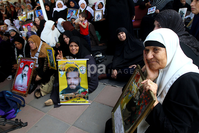Palestinian women and children hold pictures of jailed relatives during a protest calling for the release of Palestinian prisoners from Israeli jails at the Red Cross office in Gaza City on November 1,2010 . Photo by Ashraf Amra