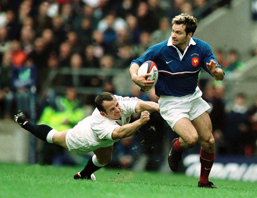 Photo. Peter Spurrier.Lloyds TSB Six Nations Championship. England vs France.at Twickenham. 07/04/2001..French wing, Christophe Dominici slips Austin Healey's flying tackle... ...........