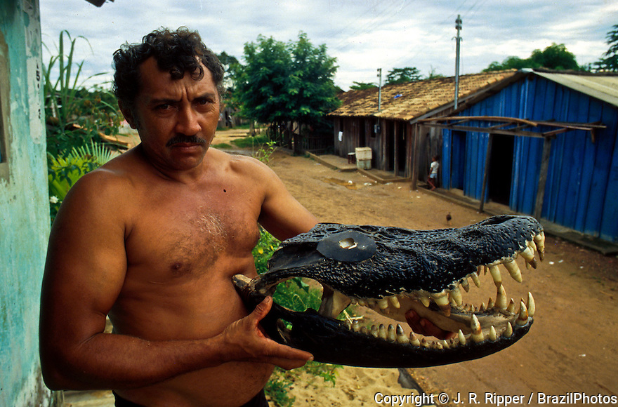 Fisherman holds a cayman head, Conceição do Araguaia, Pará State, Amazon rainforest, Brazil.