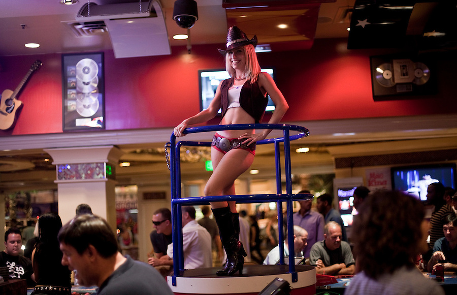 A woman in a cowboy hat and hot-pants dances as people gamble in a Las Vegas casino.
