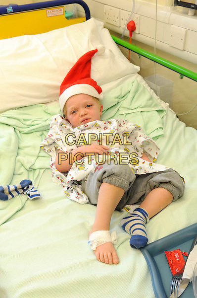 PATIENT.Patsy Kensit pays a visit to the wards of Great Ormond Street Hospital, London, UK..December 13th, 2010.sick ill full length kid child bed santa hat.CAP/FIN.©Steve Finn/Capital Pictures.
