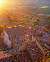 Tuscany, Italy, <br /> Evening sun on the tiled roofs of Montepulciano's houses with green farms and vineyards in the valley below