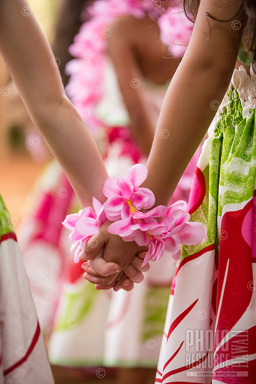 wo young girls wearing pink plumeria around their wrists hold hands before a keiki (or child) hula performance in Hale'iwa, O'ahu.