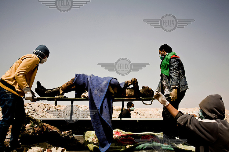 Rebels and hospital workers remove a dead Gaddafi loyalist soldier, killed during a Nato air strike on the eastern outskirts of Ajdabiya. On 17 February 2011 Libya saw the beginnings of a revolution against the 41 year regime of Col Muammar Gaddafi.