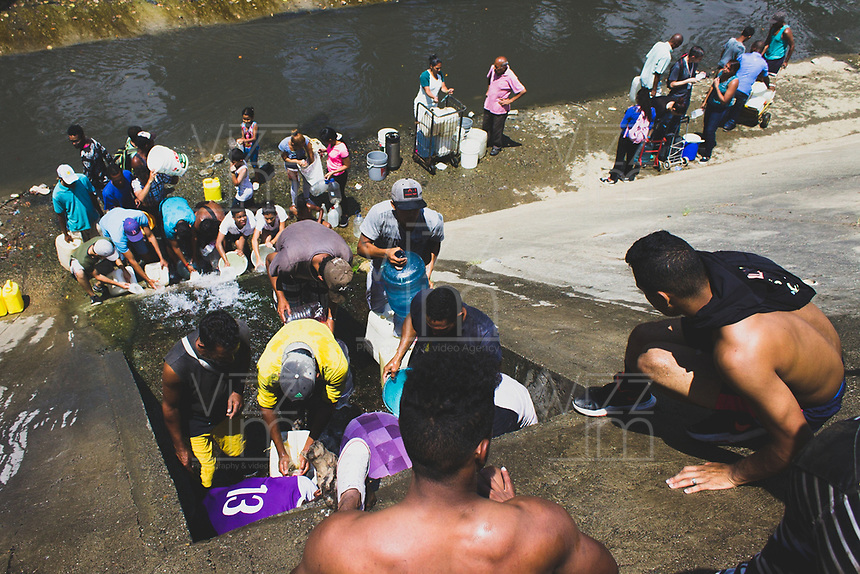 SAN AGUSTIN - VENEZUELA, 11-03-2019:  Habitantes de San Agustín tuvieron que acudir a los desagües del río Guaire para abastecerse de agua ante la creciente escasez tras el apagón en Venezuela. Otros decidieron trancar las calles y protestar hasta que les llevaron cisternas durante el 4° día de apagón que afectó Caracas y 22 estados de Venezuela debido a un fallo en Guri (Estado de Bolívar), una de las mayores represas de generación de energía eléctrica en América Latina, solo superada por la de Itaipú (entre Brasil y Paraguay). / Residents of San Agustín had to go to the drains of the Guaire River to supply themselves with water in the face of the growing shortage after the blackout in Venezuela. Others decided to block the streets and protest until they brought them cisterns during the 4th day of electricity power outage that affected Caracas and 22 states of Venezuela due to a failure in Guri (State of Bolívar), one of the largest electric power generation dams in Latin America, second only to that of Itaipú ( between Brazil and Paraguay). Photo: VizzorImage / Carolain Caraballo / Cont