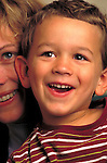 portrait of laughing toddler boy with mother