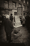 Old man with grey beard holding placards worshipping god and denouncing sinners