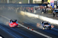 Oct. 15, 2011; Chandler, AZ, USA; NHRA funny car driver John Force (right) races alongside Jeff Diehl during qualifying at the Arizona Nationals at Firebird International Raceway. Mandatory Credit: Mark J. Rebilas-