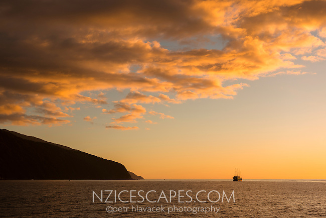 Boat and sunset over Tasman Sea in Fiordland, Fiordland National Park, Southland,  UNESCO World Heritage Area, New Zealand, NZ
