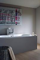 A colourful print hangs above the bath in this minimal bathroom