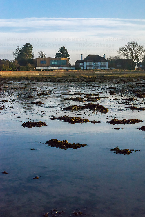 View across the estruary in Bosham looking towards old and new cottages in winter