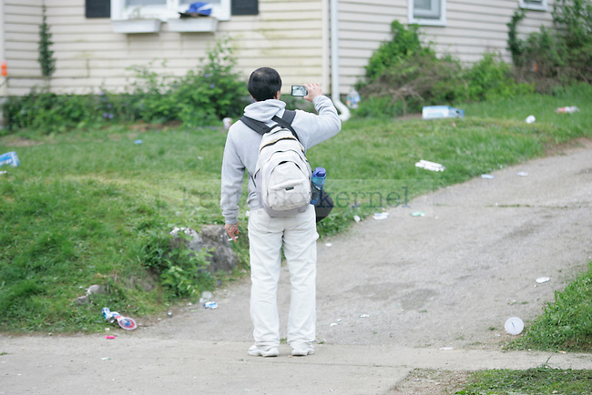A lexington resident takes video of the celebration aftermath on State St. in Lexington, Ky. on 4/1/12. Photo by Quianna Lige | Staff