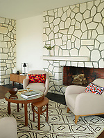 In the living area, original features like the limestone fireplace have been retained. Vibrant throw pillows by Nathalie Du Pasquier offset the neutral sofa and armchairs from Habitat and the Moroccan rug. Vintage English occasional and coffee tables stand at the room's centre. Ceramics and objects from Guilaume Bardet, Jonathan Adler and Ferm Living accent the space.