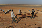 A.G, right, an Eritrean labourer working for an Israeli construction company, and his fellow Eritrean labourer, work on the construction of a barrier at Israel-Egypt border, some 70 km north of Eilat, southern Israel. Alarmed by what it described as a near-doubling in the influx of Africans seeking work or claiming refugee status, Israel last year began erecting a fence along the frontier.