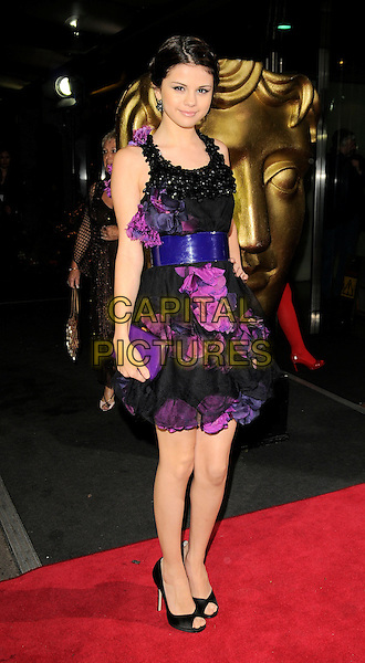 SELENA GOMEZ.The British Academy Children's Film and Television Awards, London, Hilton Hotel, Park Lane, London, England..November 30th, 2008.BAFTA BAFTA's full length black purple dress sheer flowers corsages clutch bag open toe shoes waist belt .CAP/CAN.©Can Nguyen/Capital Pictures.