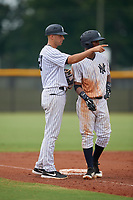 GCL Yankees East manager Dan Fiorito (27) talks with Sandy Mota (11) during a Gulf Coast League game against the GCL Phillies East on July 31, 2019 at Yankees Minor League Complex in Tampa, Florida.  GCL Phillies East defeated the GCL Yankees East 4-3 in the second game of a doubleheader.  (Mike Janes/Four Seam Images)